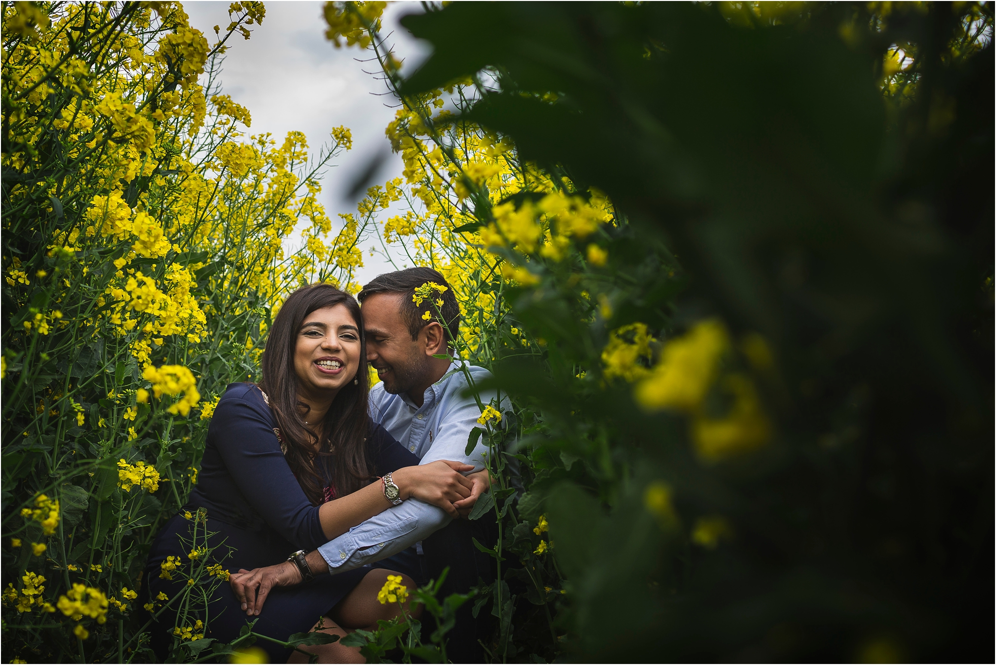 A couple cuddling and laughing whilst sat amongst yellow rape seed at Shrewley Pool Farm in Warwickshire
