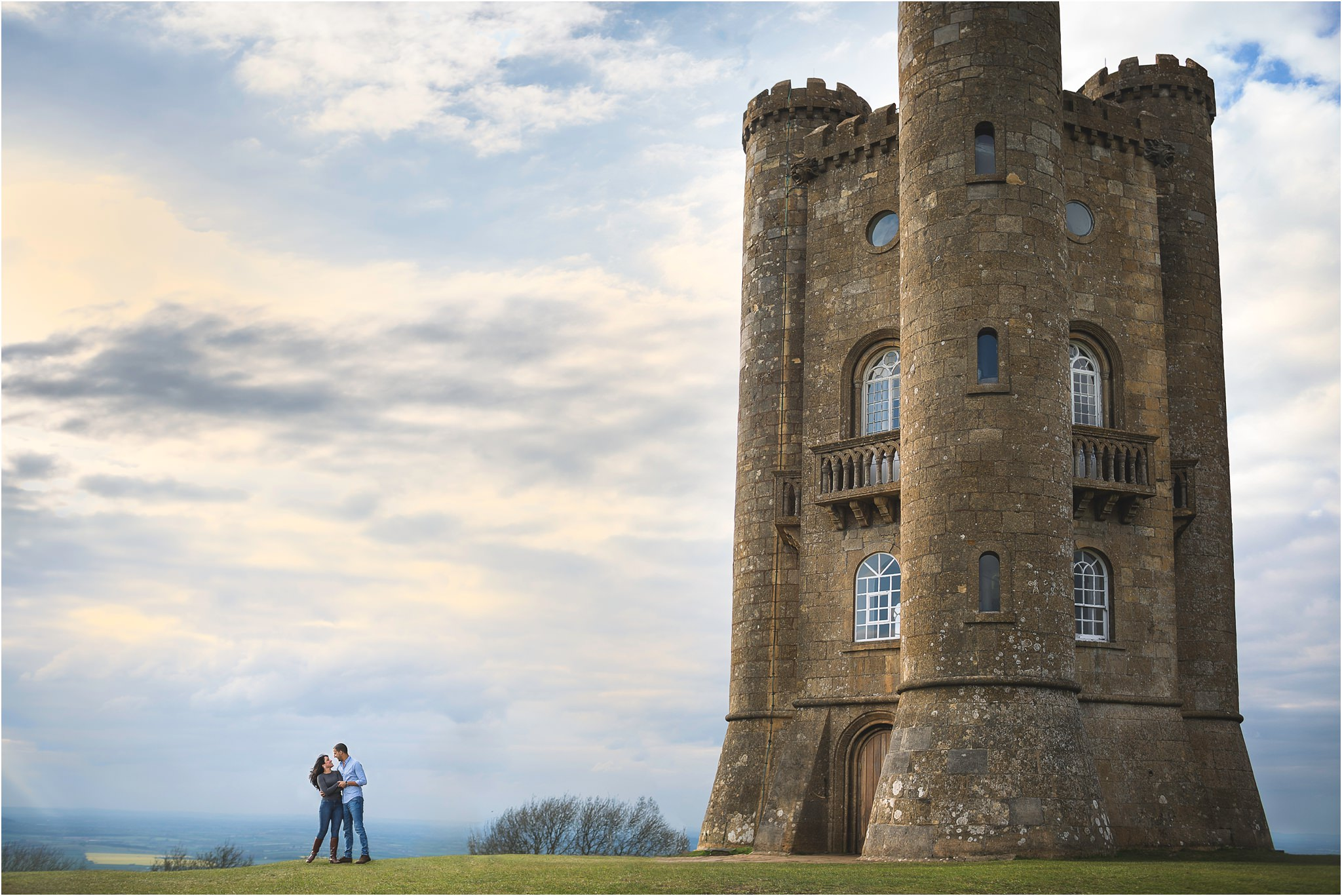 A couple in front of Broadway Tower in Worcestershire with a moody sky.