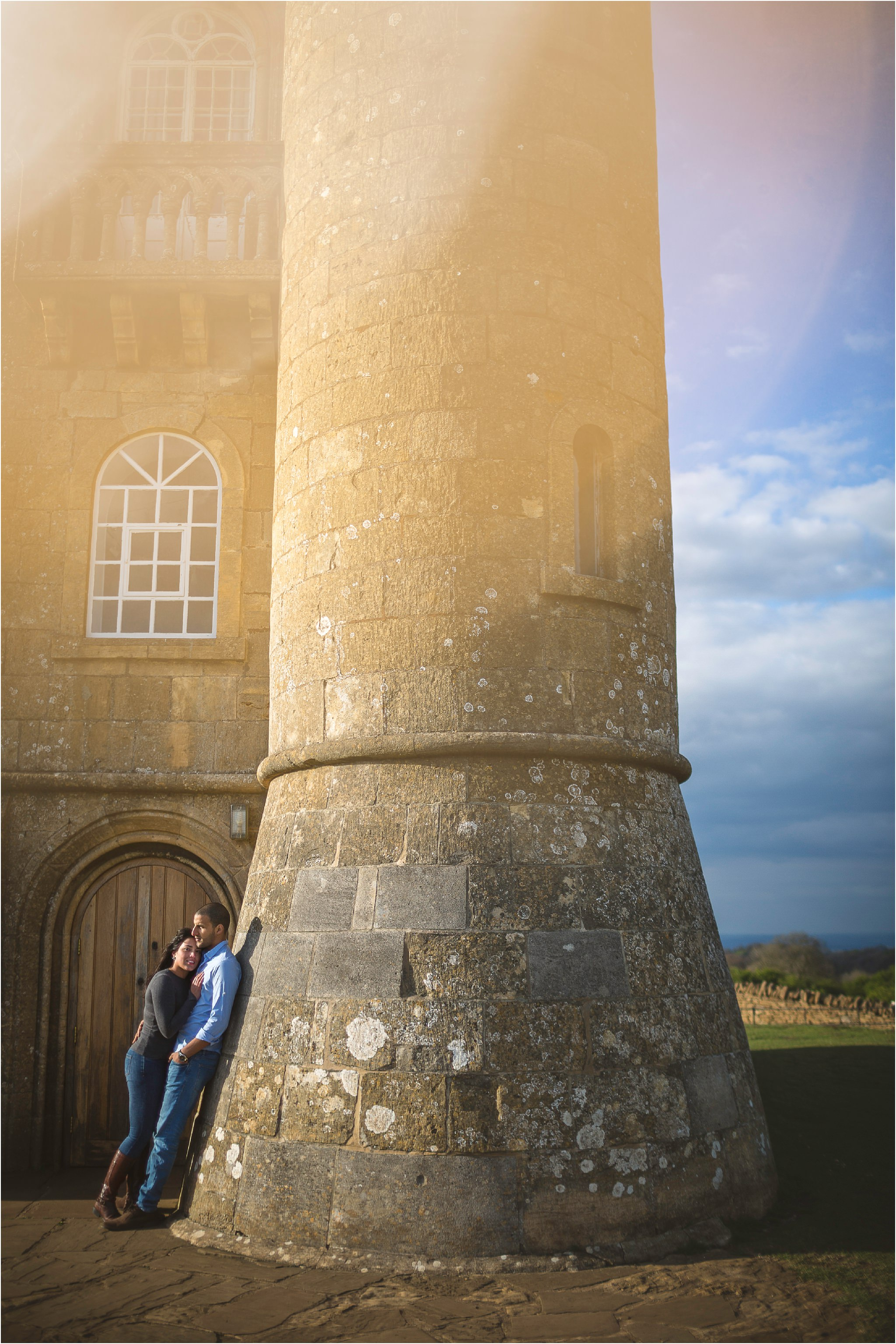 Bride to be hugging her fiance in front of Broadway Tower in Worcestershire with a orange flare effect coming from the top of the image.