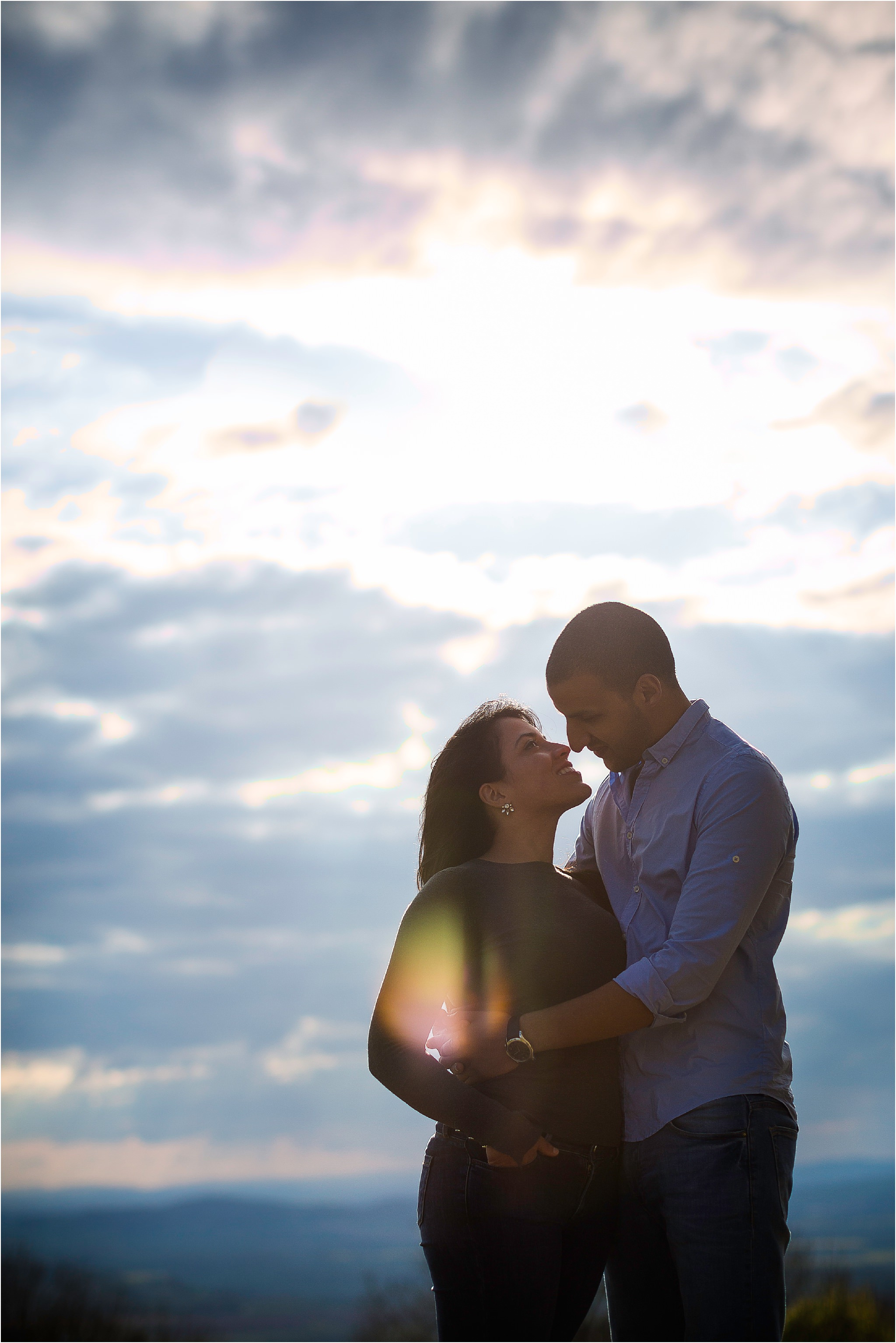 A coupe just about to kiss during their pre wedding shoot in Worcestershire, with dramatic sky and lens flare.