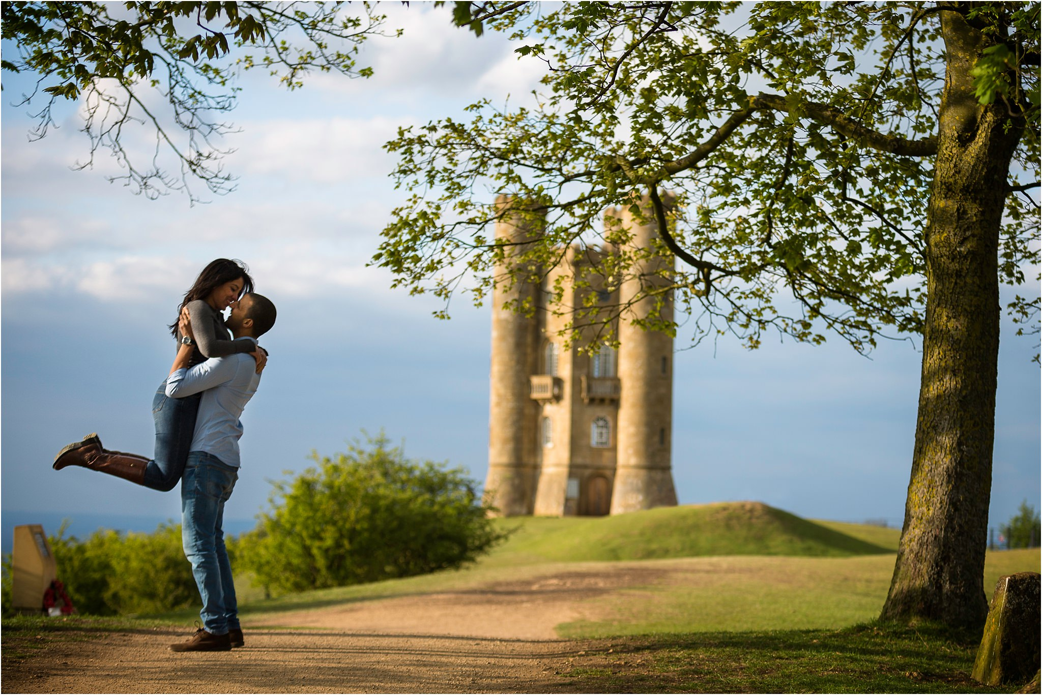 A man picking up his wife to be for a kiss in front of Broadway Tower in Worcestershire. This was part of their pre wedding shoot in The Cotwolds.