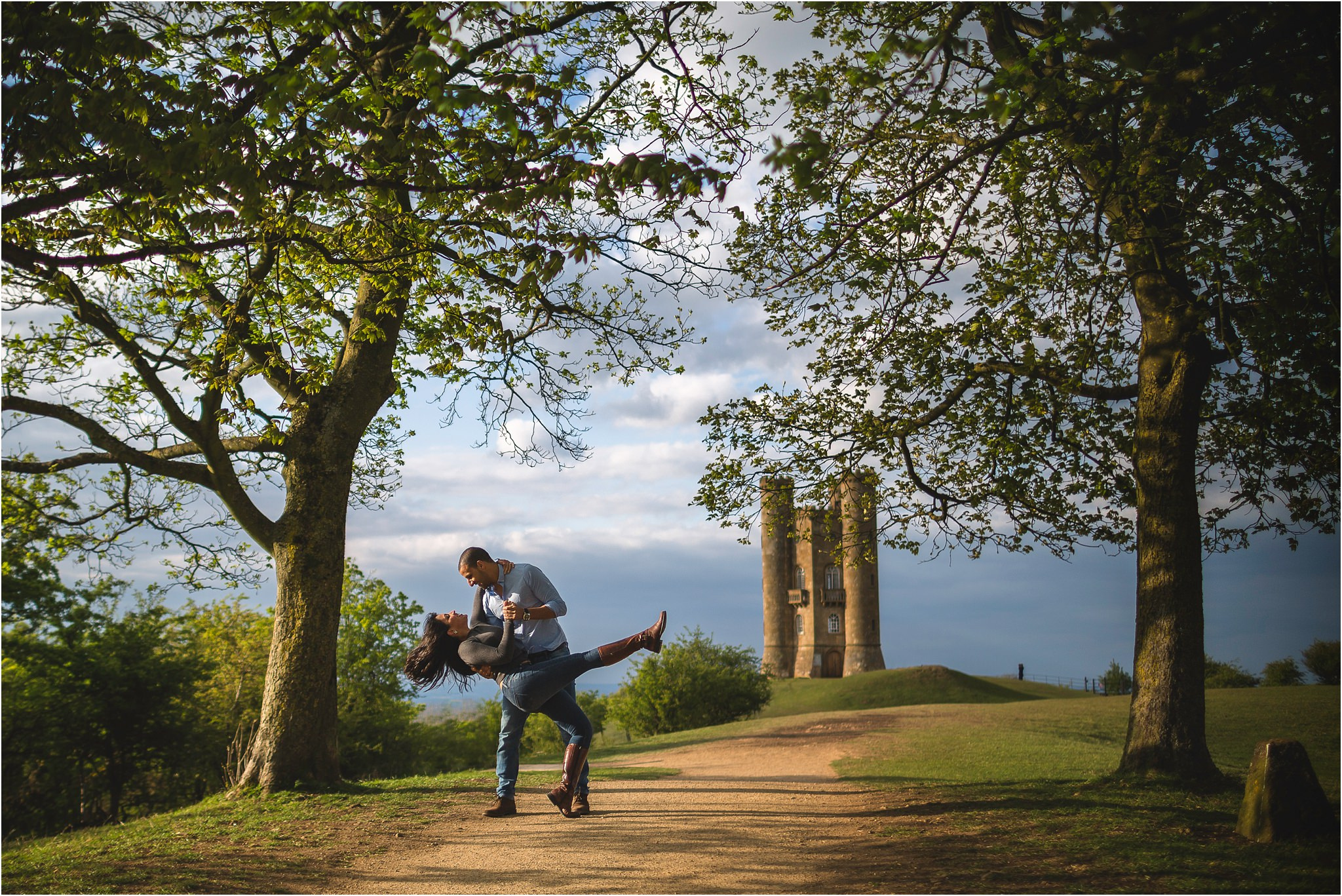 Couple dancing, with the man dipping the girl whilst she kicks her leg out. They are surrounded by trees with Broadway Tower in the background.