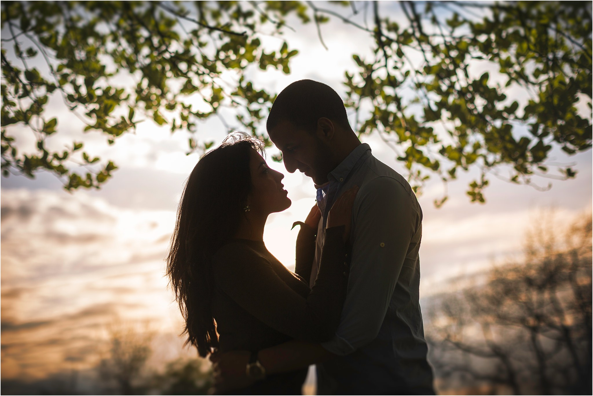 A slightly silouetted image of a couple about to kiss with orange sky to the bottom of the image and branches of leaves behind them at the top of the image.