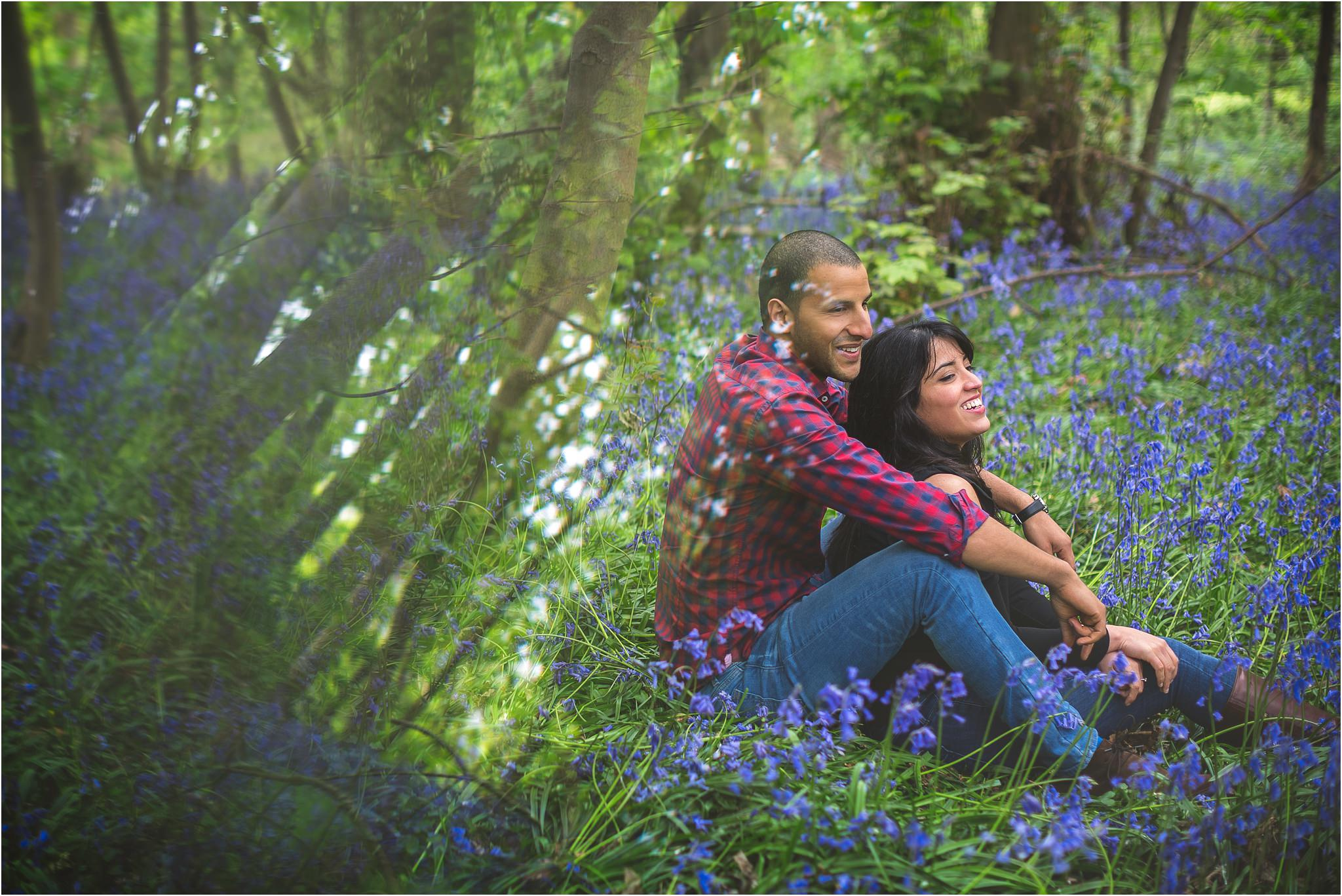 Couple sitting amongst bluebells with a reflective effect in the left side of the image.