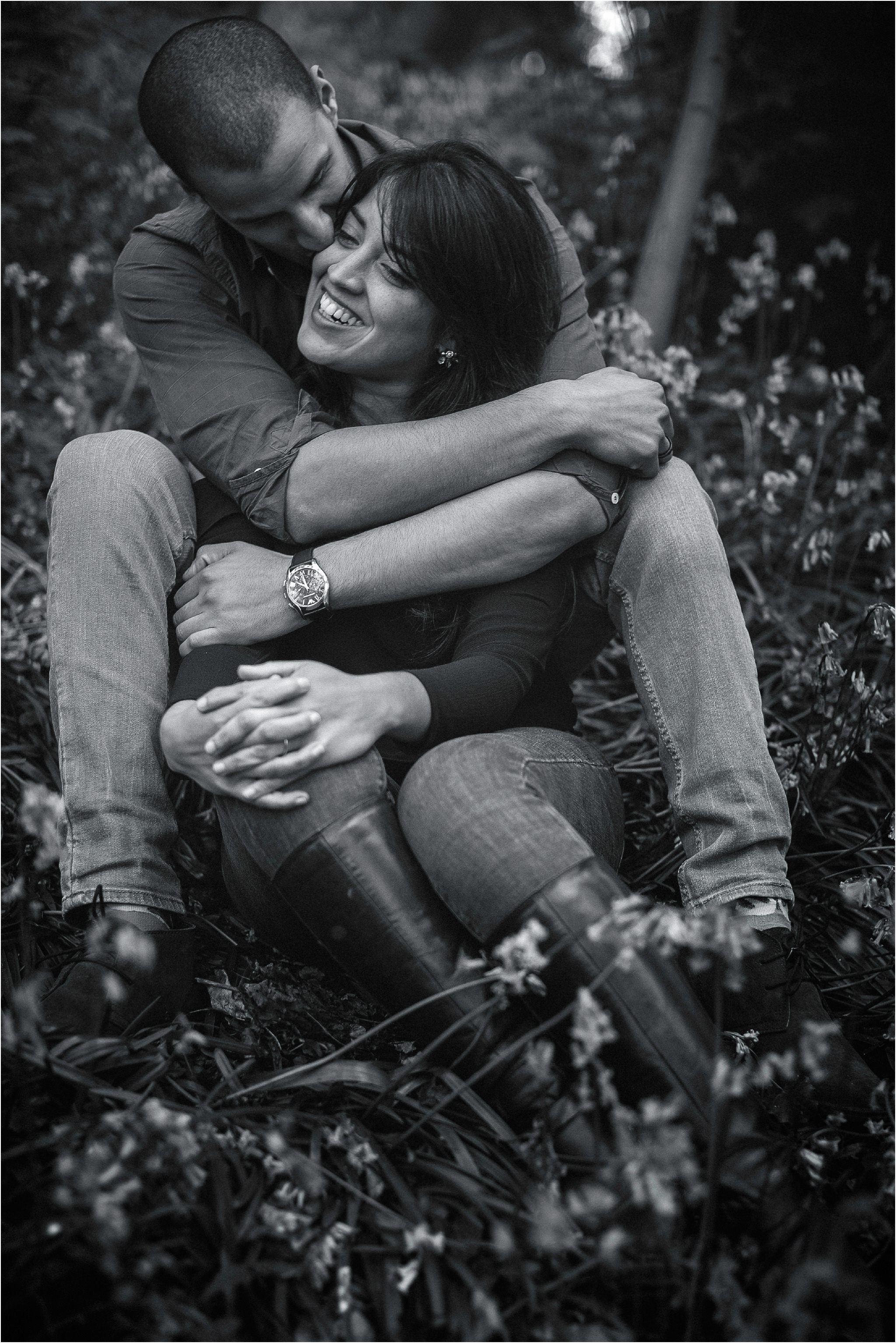 Black and white image of a couple cuddling amongst bluebells. The man is kissing his lady on the cheek whilst she smiles.