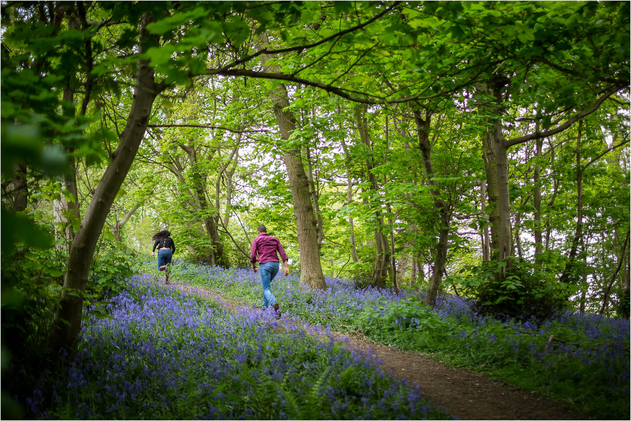 Couple racing up a hill amongst bluebells on the grounds of The Fish Hotel in the Costwolds