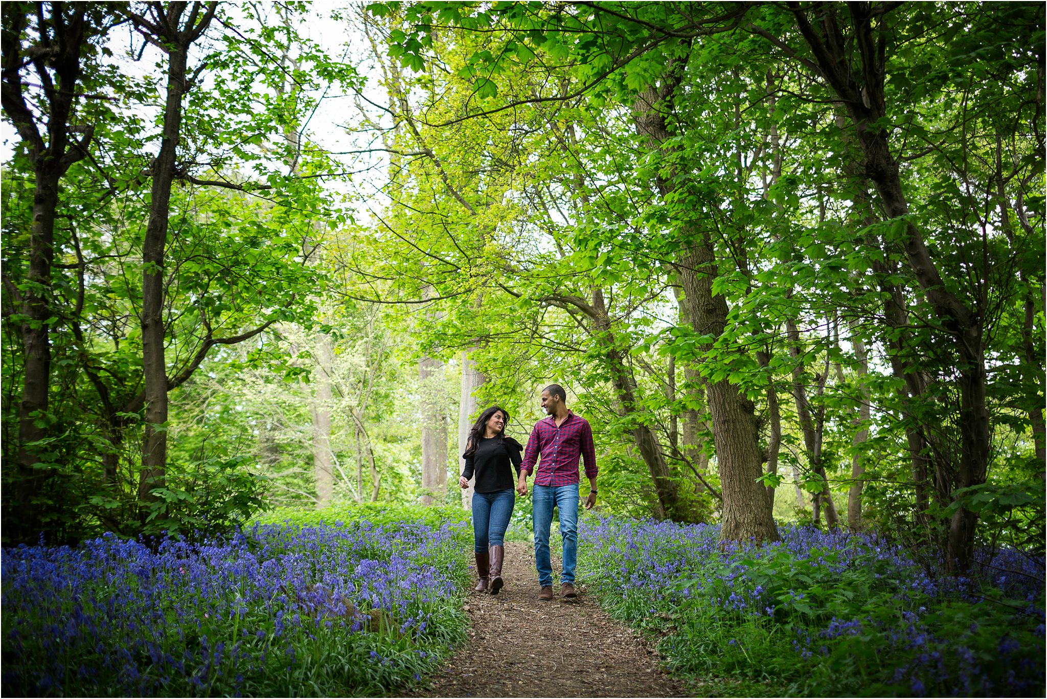 Cotwolds pre wedding photo shoot at The Fish Hotel. Couple holding hands walking down a hill amongst bluebells.