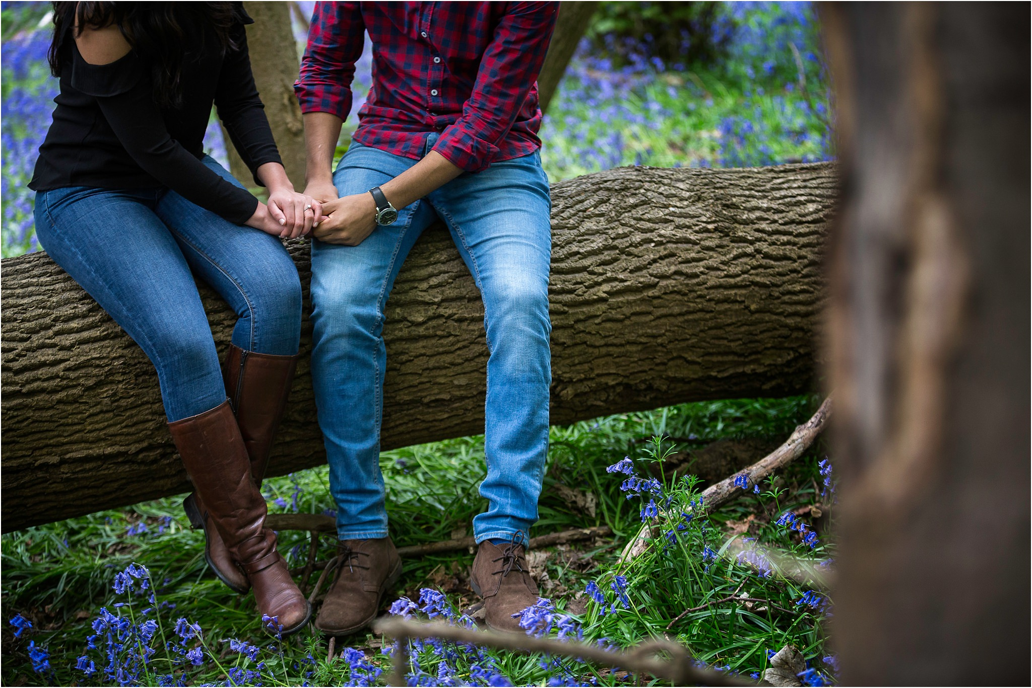 Close up of couple holding hands, sat on a broken down tree.