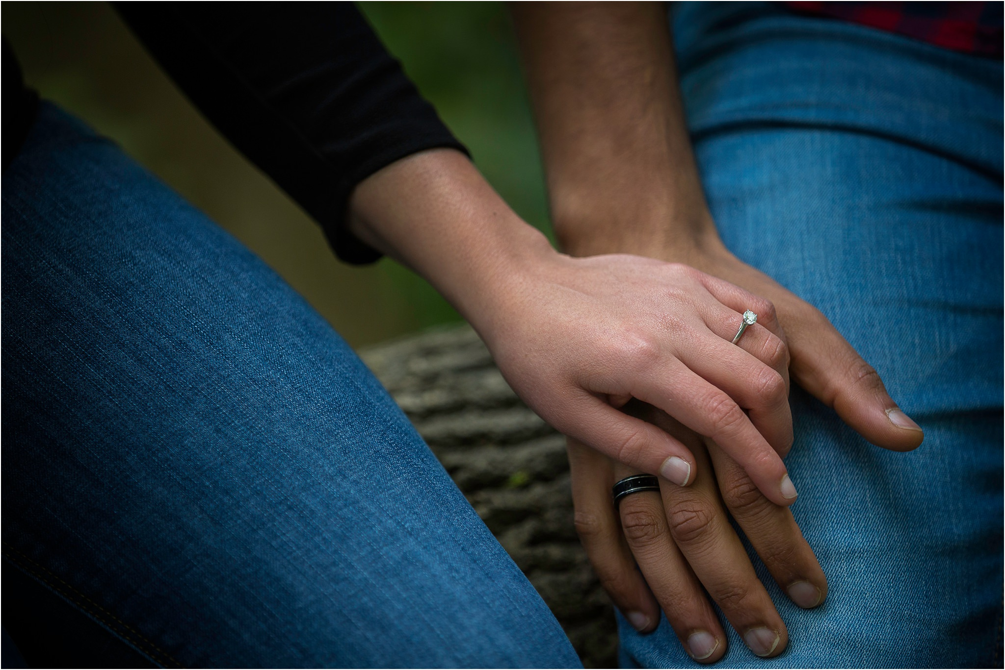 Close up of a couples hands. The lady has her engagement ring on show, whilst the mans hand is underneath.