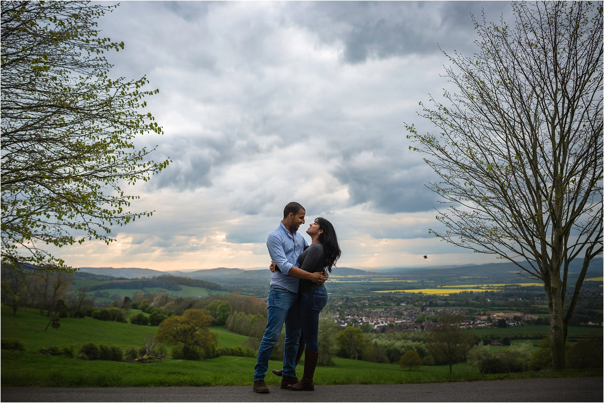 couple smiling at each other in front of beautiful costwolds countryside