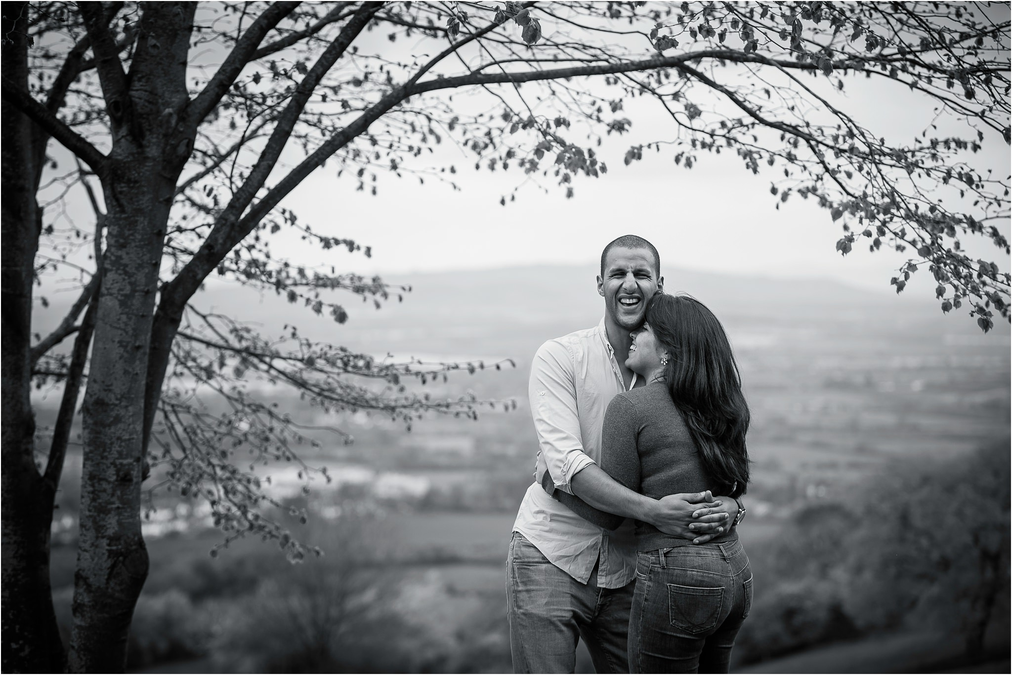 black and white image of couple cuddling whilst laughing hysterically