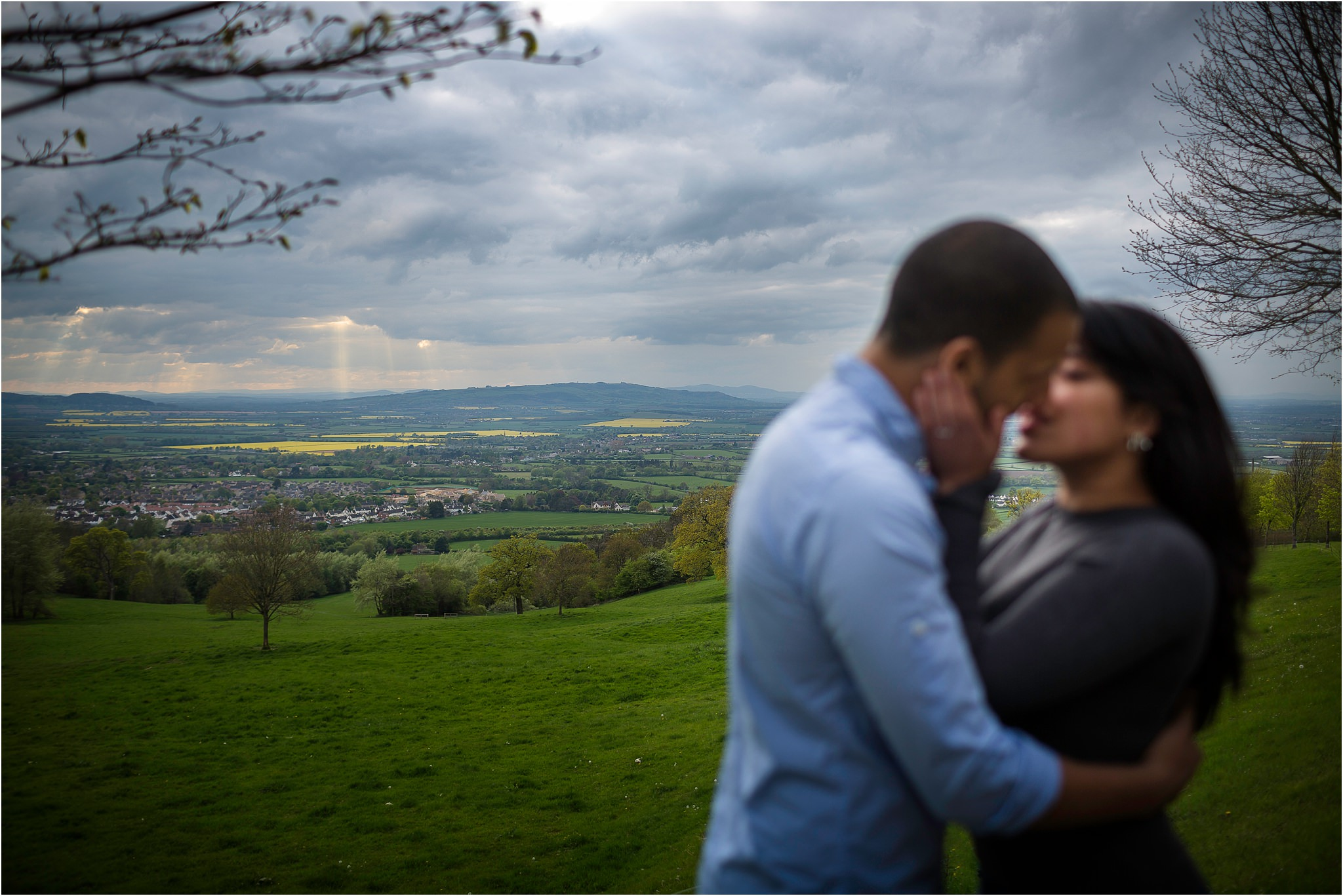 couple out of focus, kissing, with main focus being of the beautiful countryside behind them
