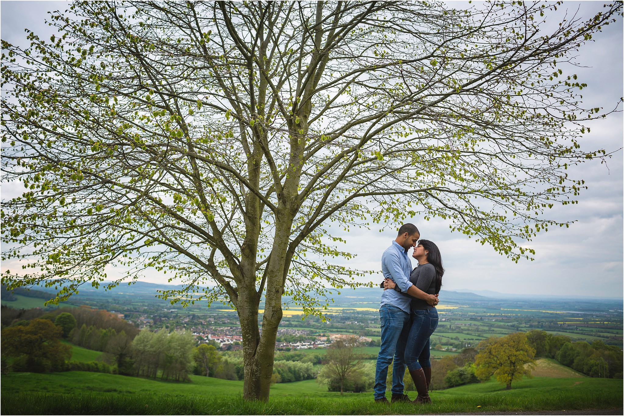 couple about to kiss, next to a tree and in front of beautiful English countryside.