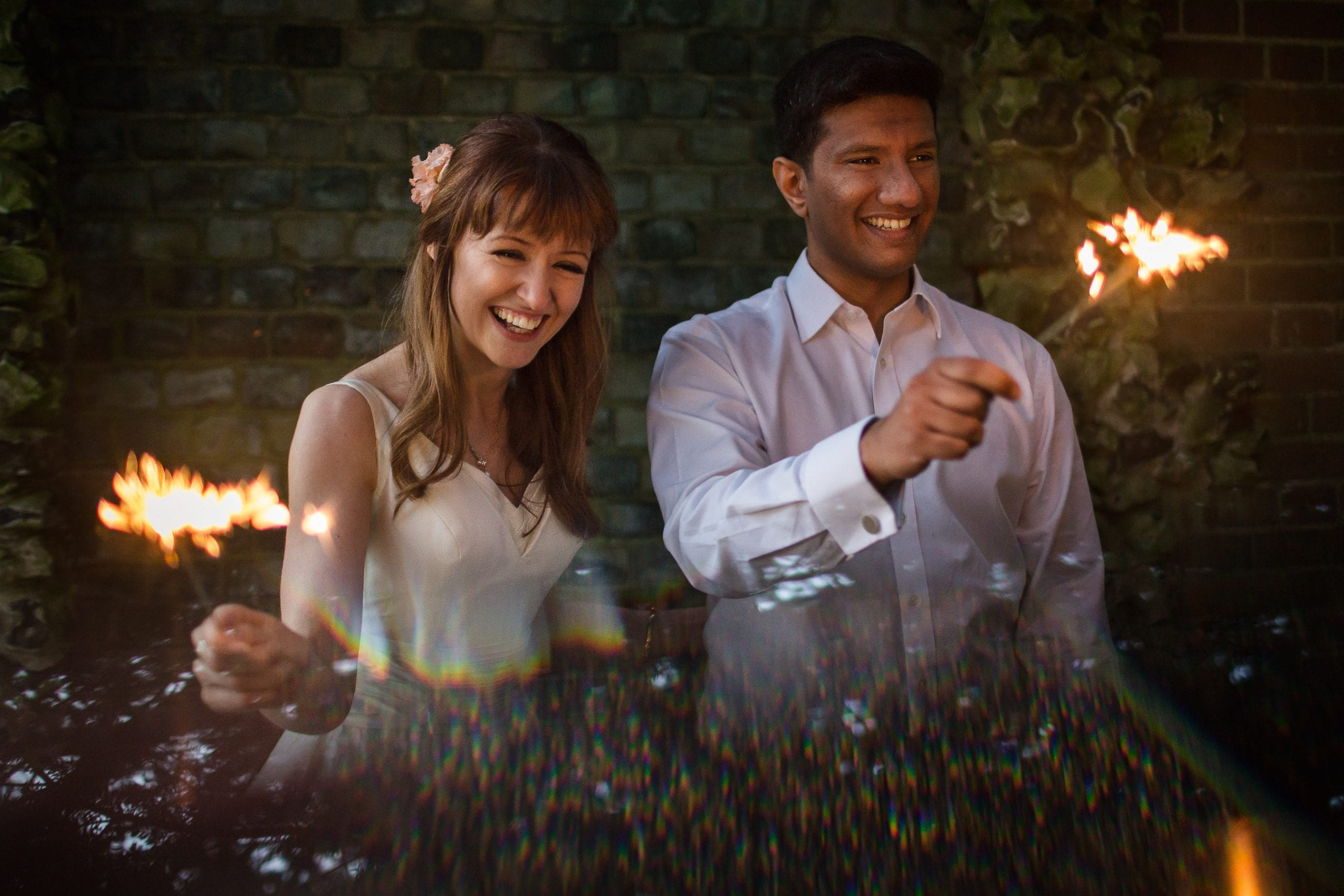 a couple having fun playing with sparklers on their wedding day