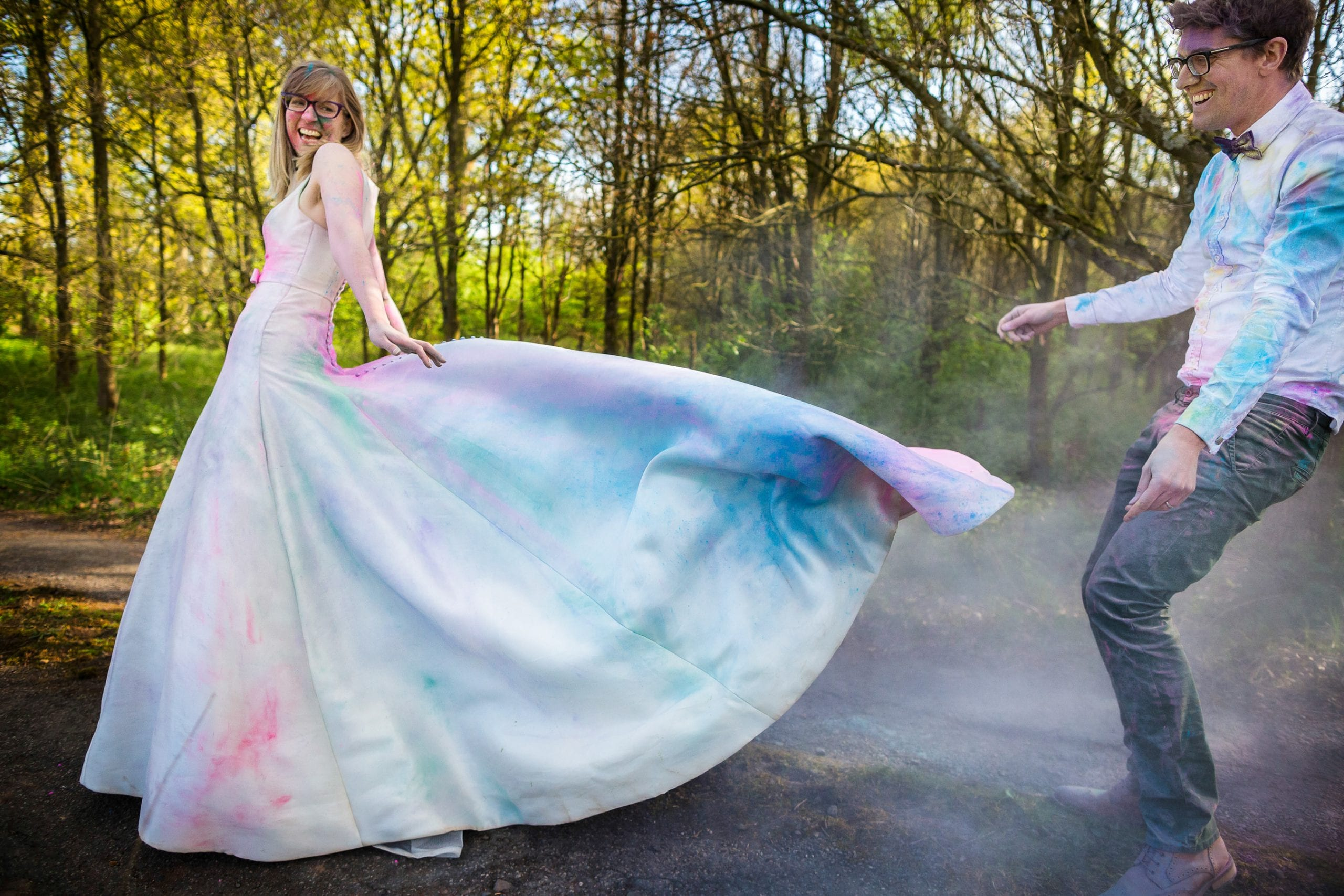 A trash the wedding dress photoshoot, with the brides dress covered in coloured powder - being flung in the air. Both the bride and groom are laughing. By Warwickshire wedding photographer, S2 Images