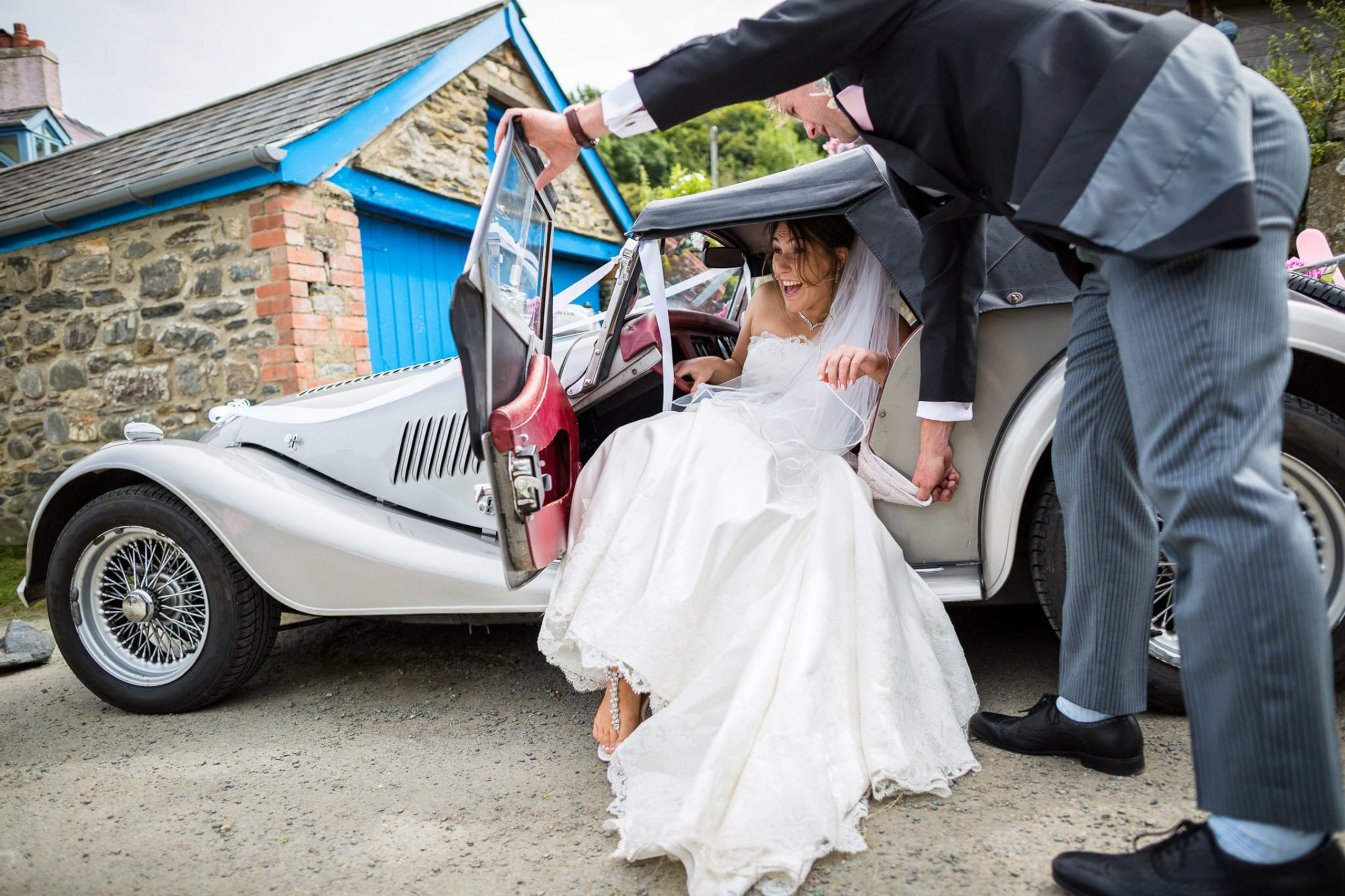 Cotswolds Wedding Photographers in Fishguard, Wales. A bride getting out of a low sports car, with help from the groom.