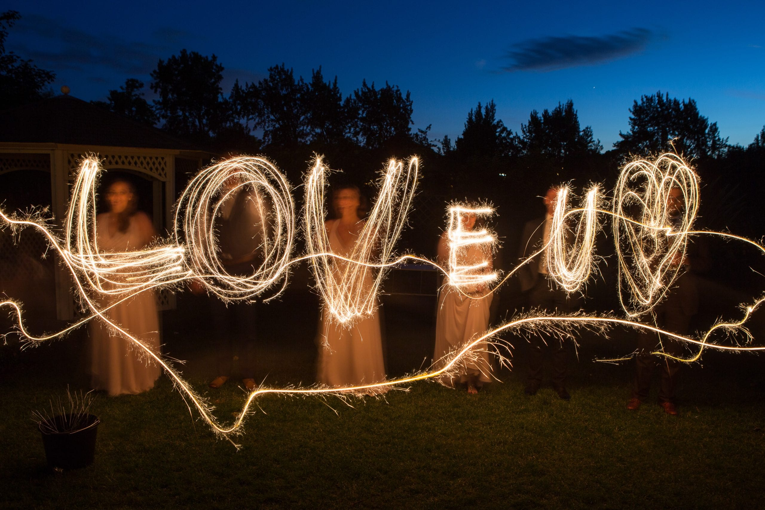 Bridesmaids and groomsmen spelling out LOVE U in sparklers at Warwick House.
