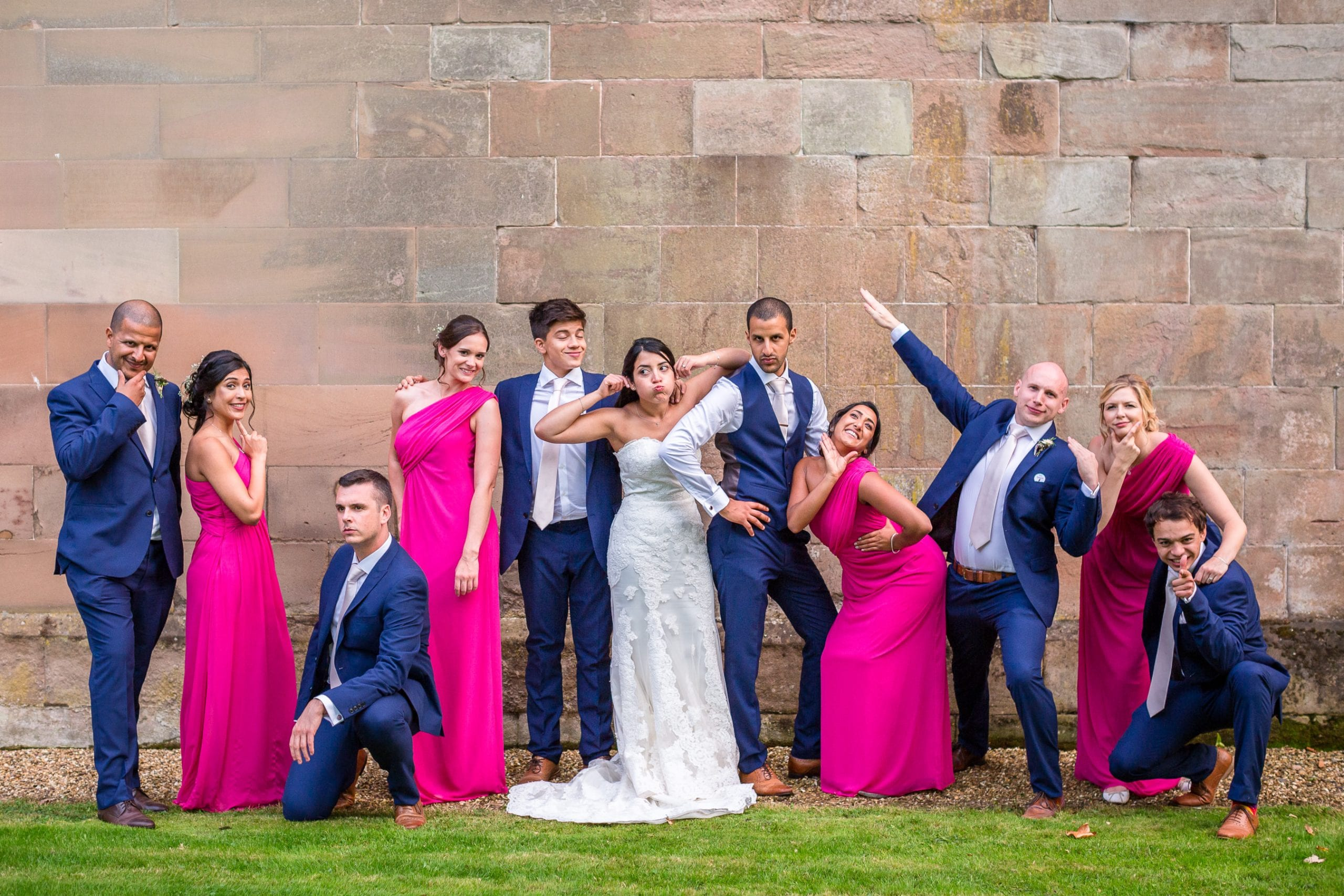 Bridemaids and groomsmen doing silling poses for a group shot at Stoneleigh Abbey in Warwickshire.