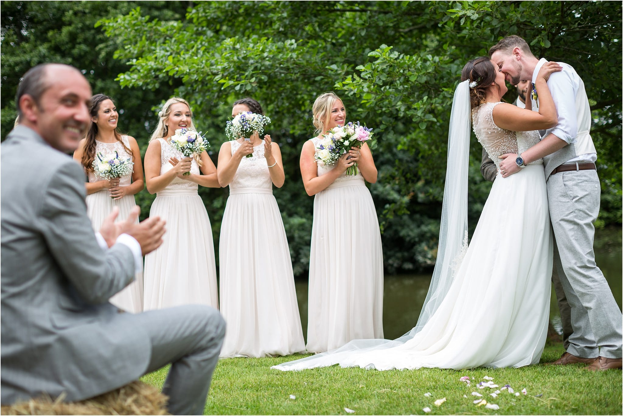 Couple's first kiss as husband and wife. Bridesmaids clapping whilst father of the bride looks away and smiles.