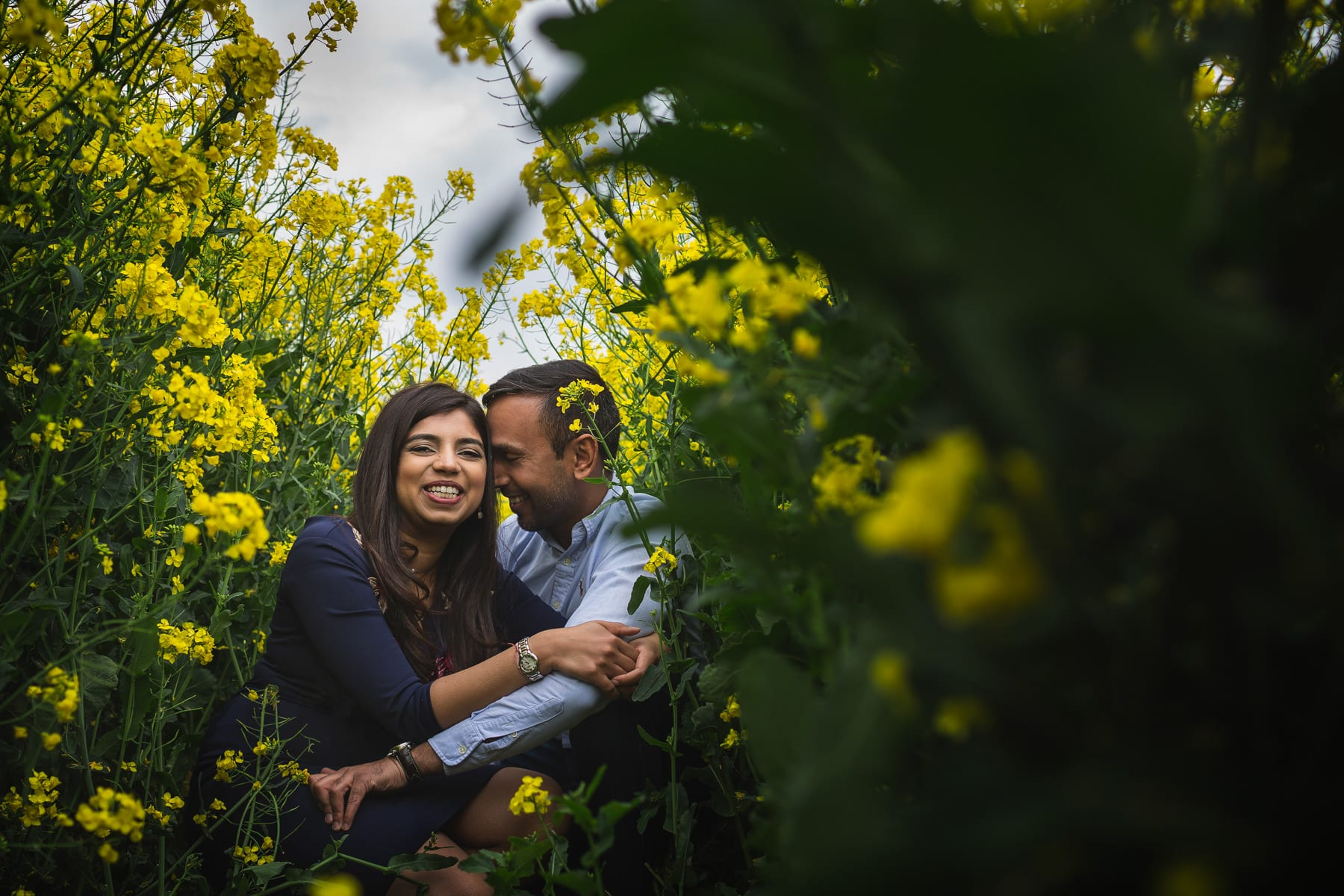 A warwickshire pre wedding photo shoot in a rape seed field full of yellow flowers.