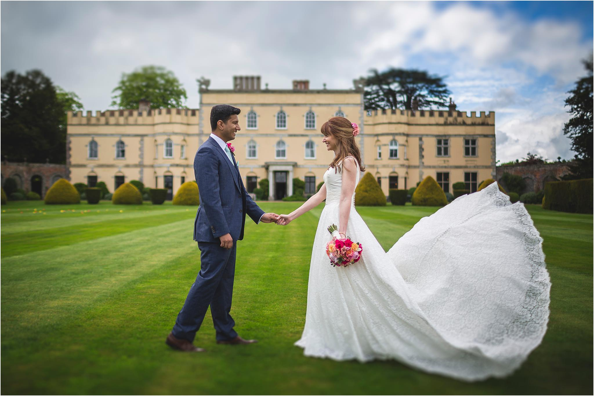 A bride and groom coming together in front of their wedding venue. The brides dress train has been flung in the air. Image by S2 Images, Hampden House Wedding Photographer