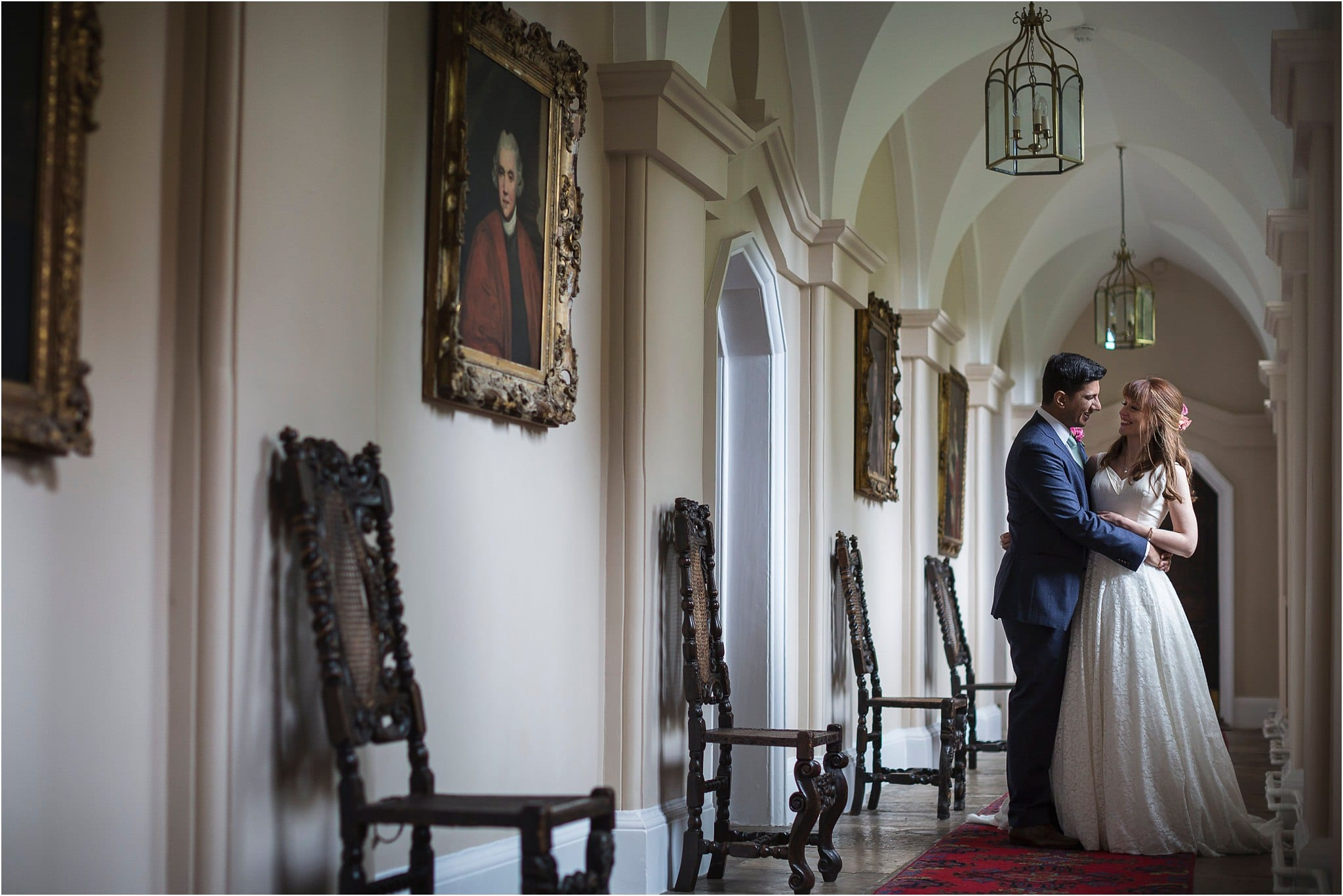 A couple coming together for a photograph, down a corridor with old paintings in. Image by S2 Images, Hampden House Wedding Photographer