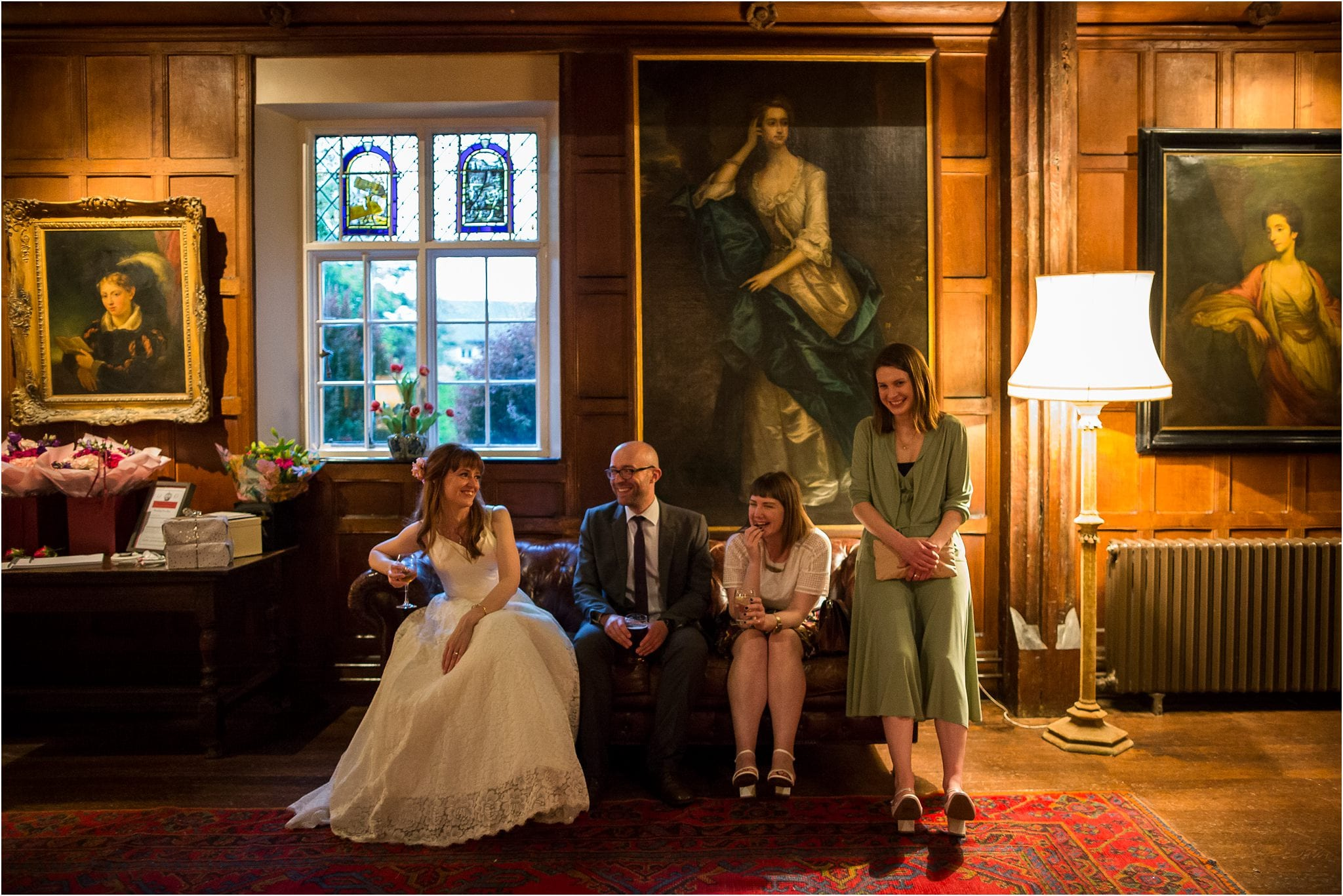 Guests and the bride relaxing on a sofa in front of a large painting in a grand room. Image by S2 Images, Hampden House Wedding Photographer