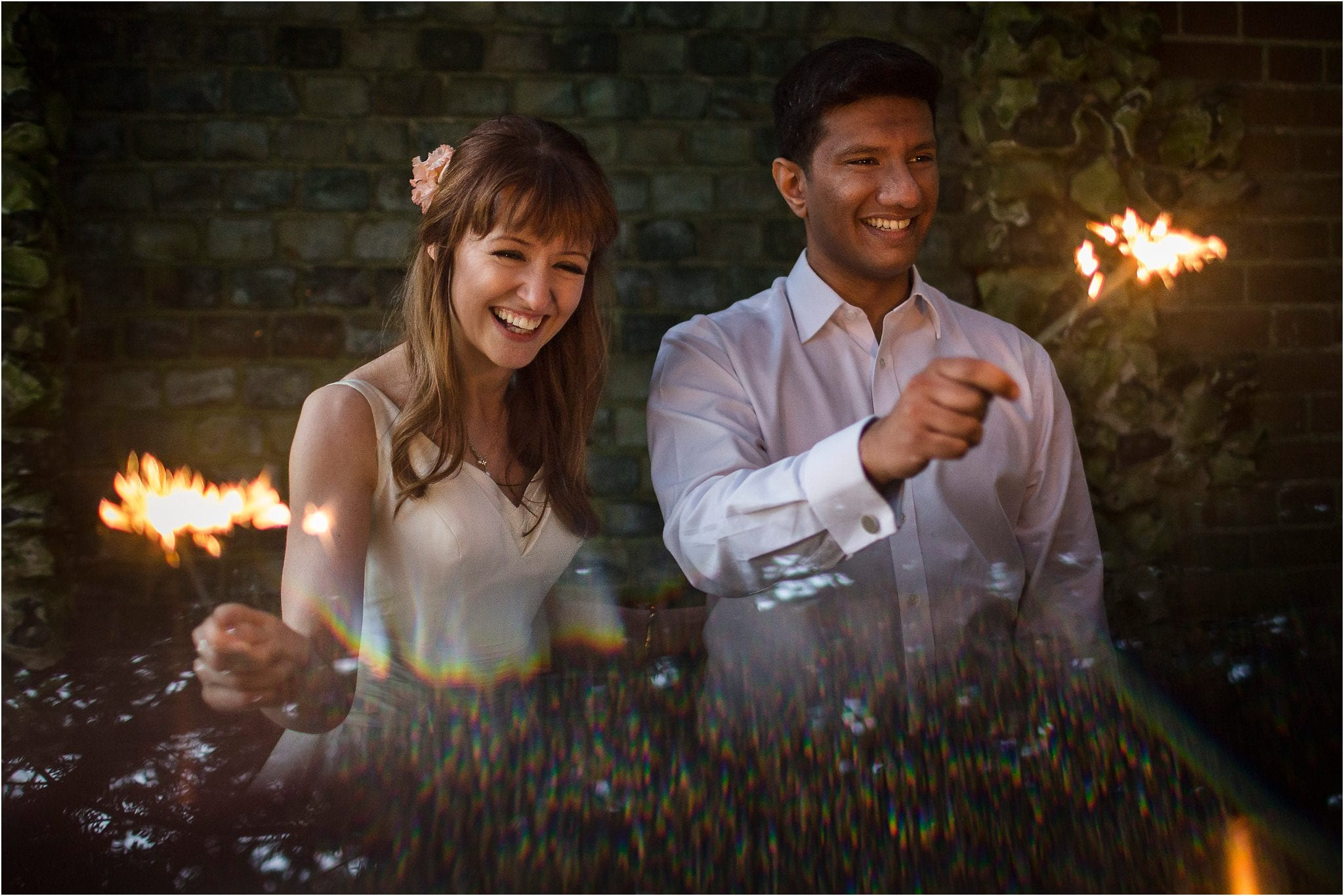 A bride and groom playing with sparklers on their wedding day. Image by S2 Images, Hampden House Wedding Photographer
