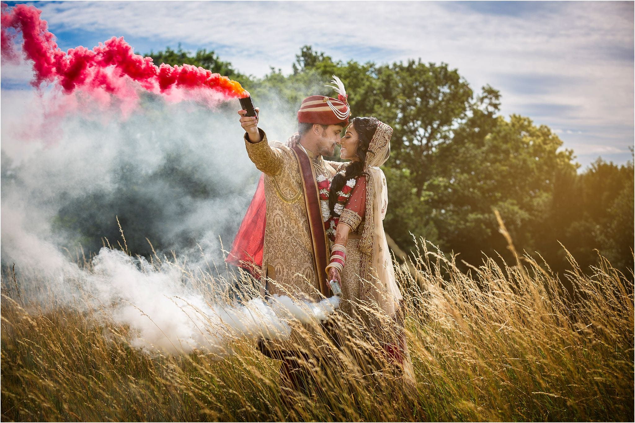 An couple in Asian attire kissing whilst holding coloured smoke grenades. Photography by Hedsor House wedding photographer S2 Images