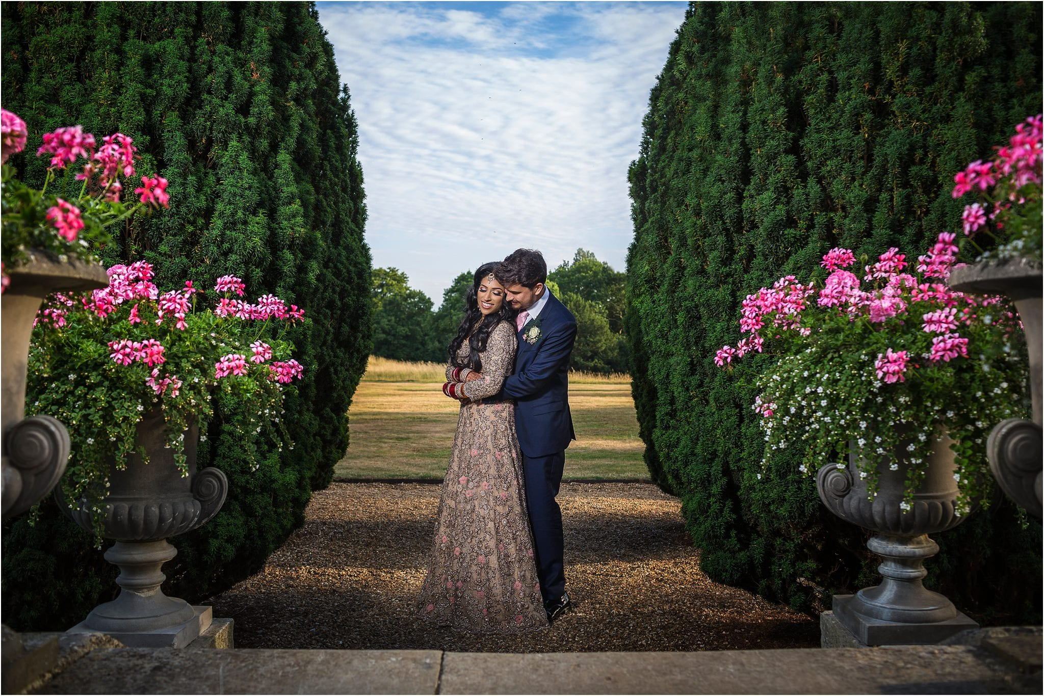 A couple hugging amongst trees and and pink flowers. Photography by Hedsor House wedding photographer S2 Images