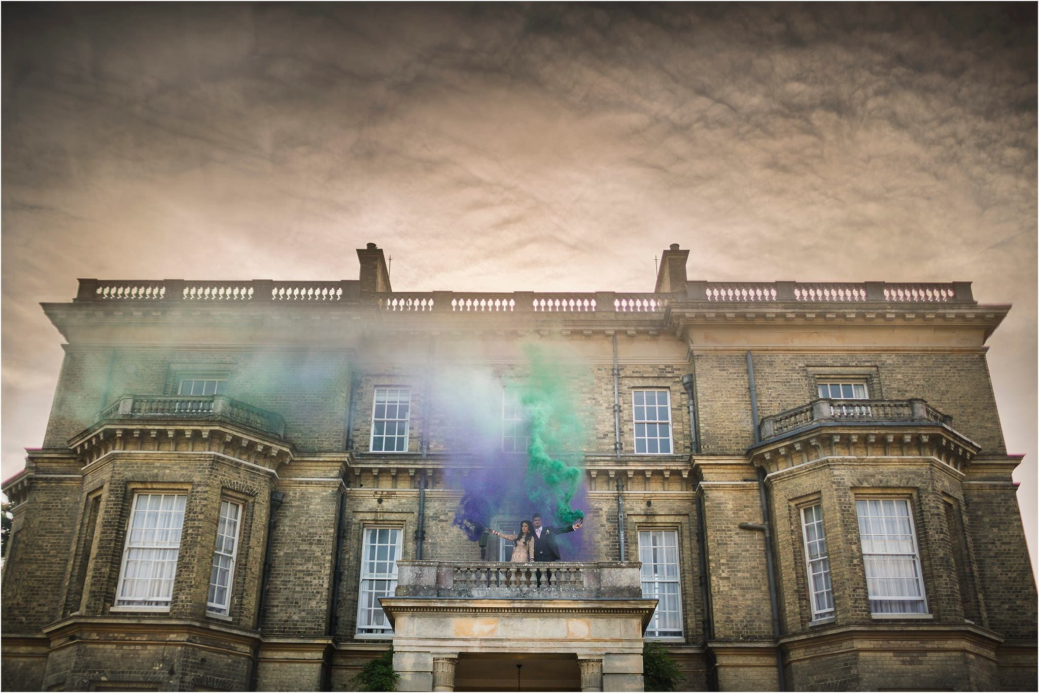 A grand wedding venue, Hedsor House. The sky is moody and there is a couple holding purple and green smoke grenades on a balcony in the middle of the image.