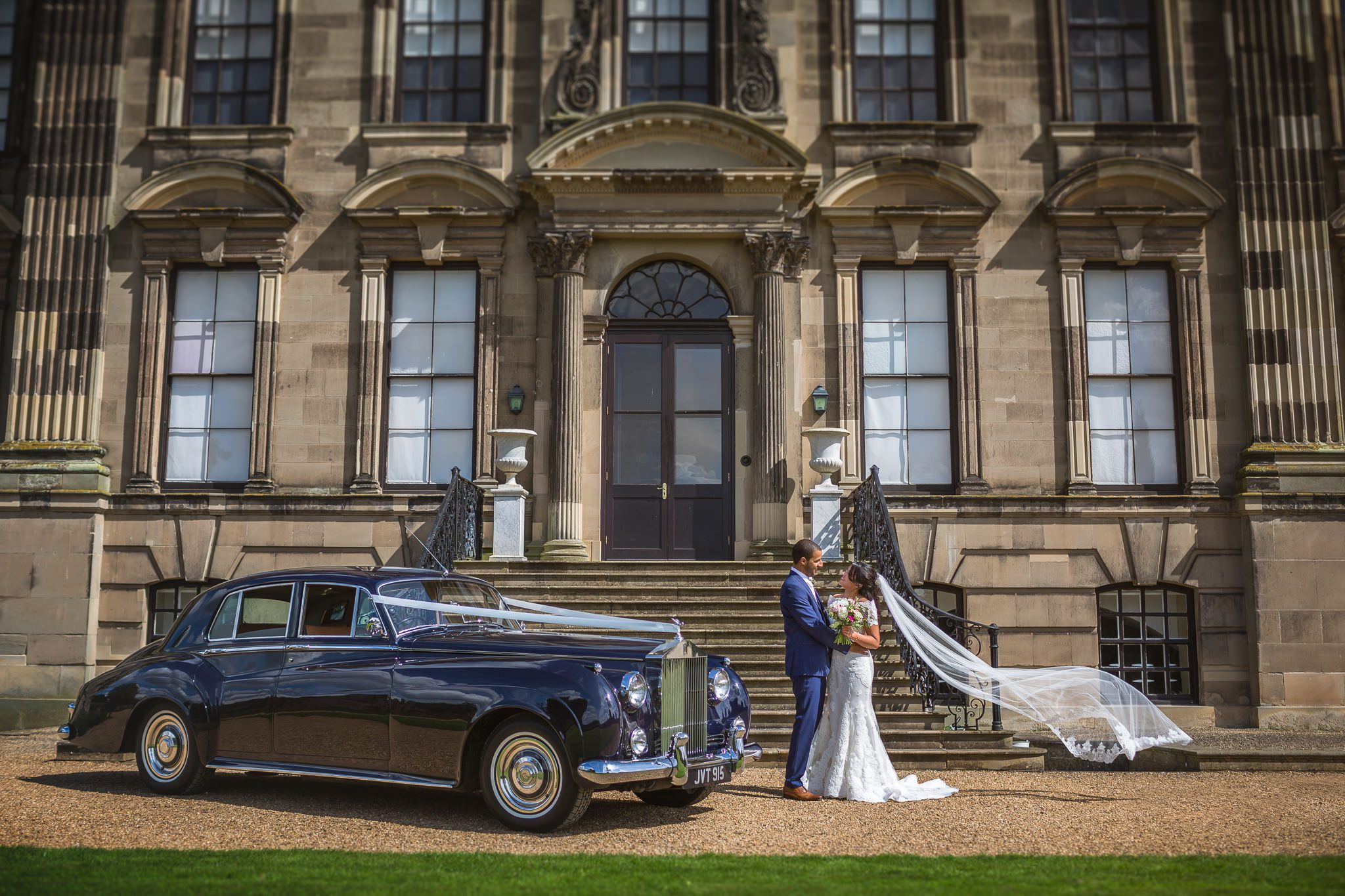 A couple in front of a grand building by Stoneleigh Abbey Wedding Photographer, S2 Images