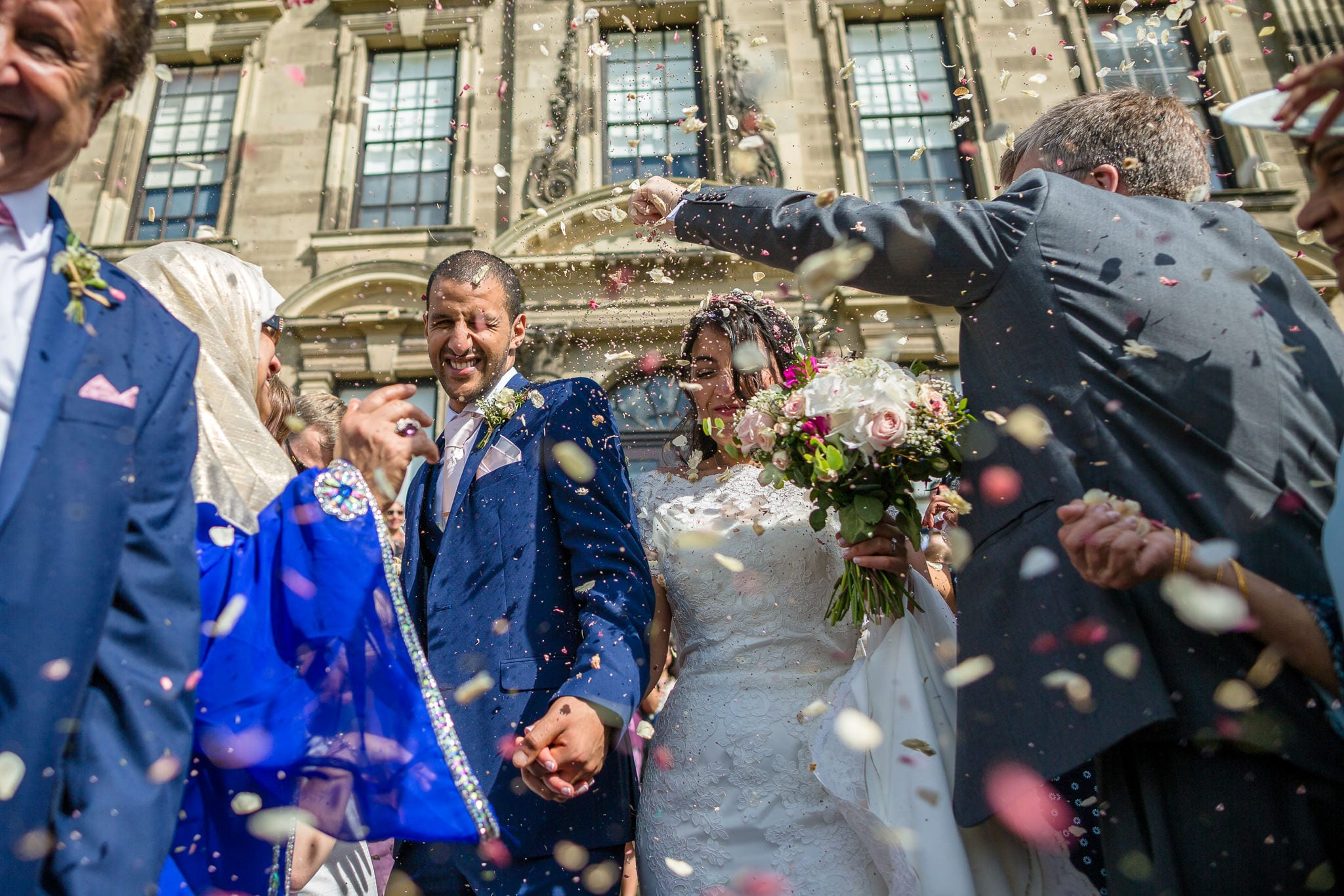 Bride and groom being covered with confetti by their guests. by Stoneleigh Abbey Wedding Photographer, S2 Images