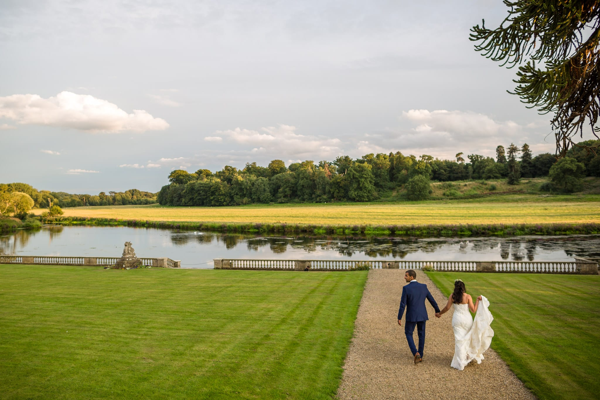 Bride and groom holding hands whilst walking towards a beautiful river. by Stoneleigh Abbey Wedding Photographer, S2 Images