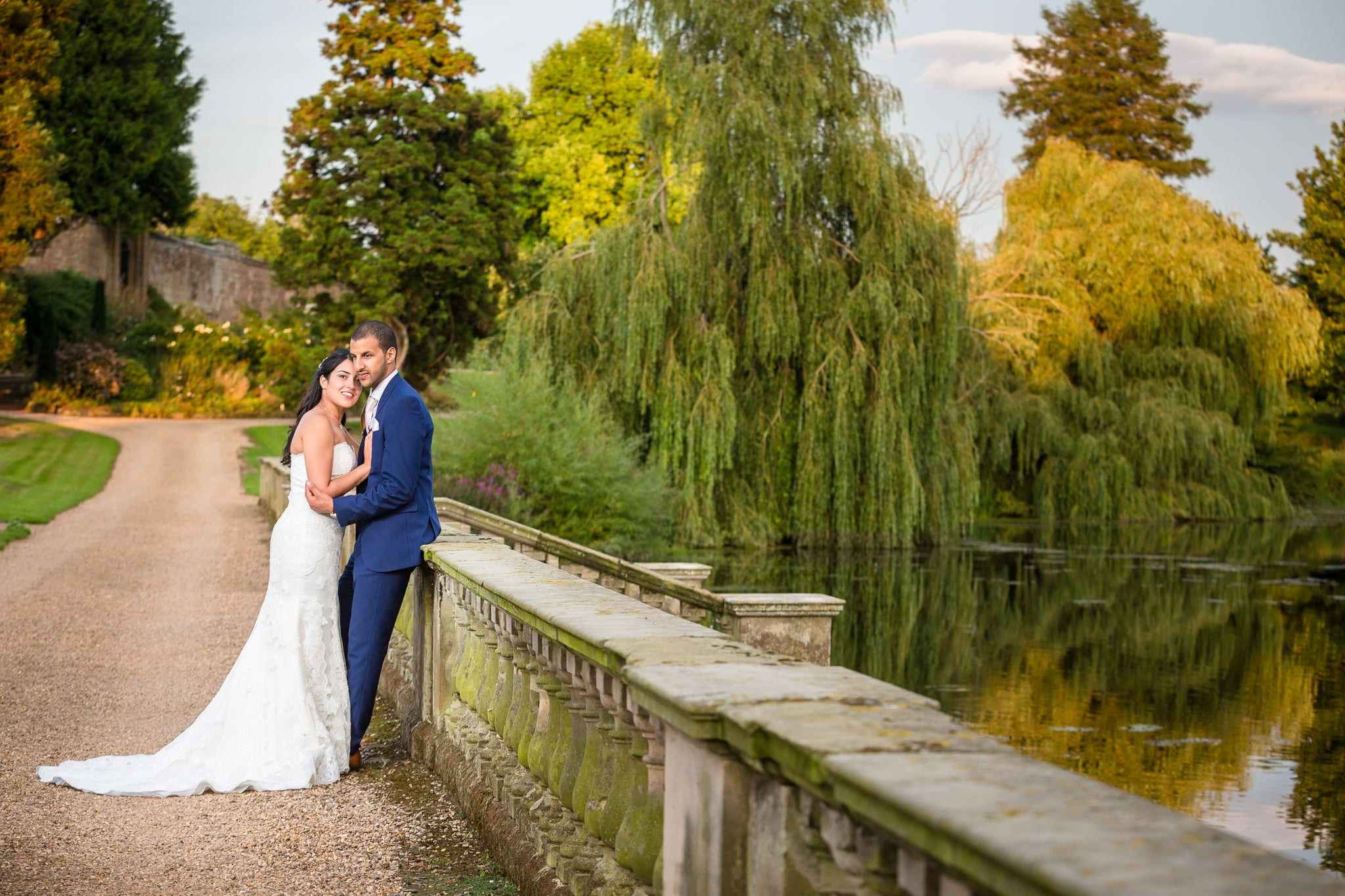 A bride and groom coming together for a photo in front of a beautiful river and trees. by Stoneleigh Abbey Wedding Photographer, S2 Images