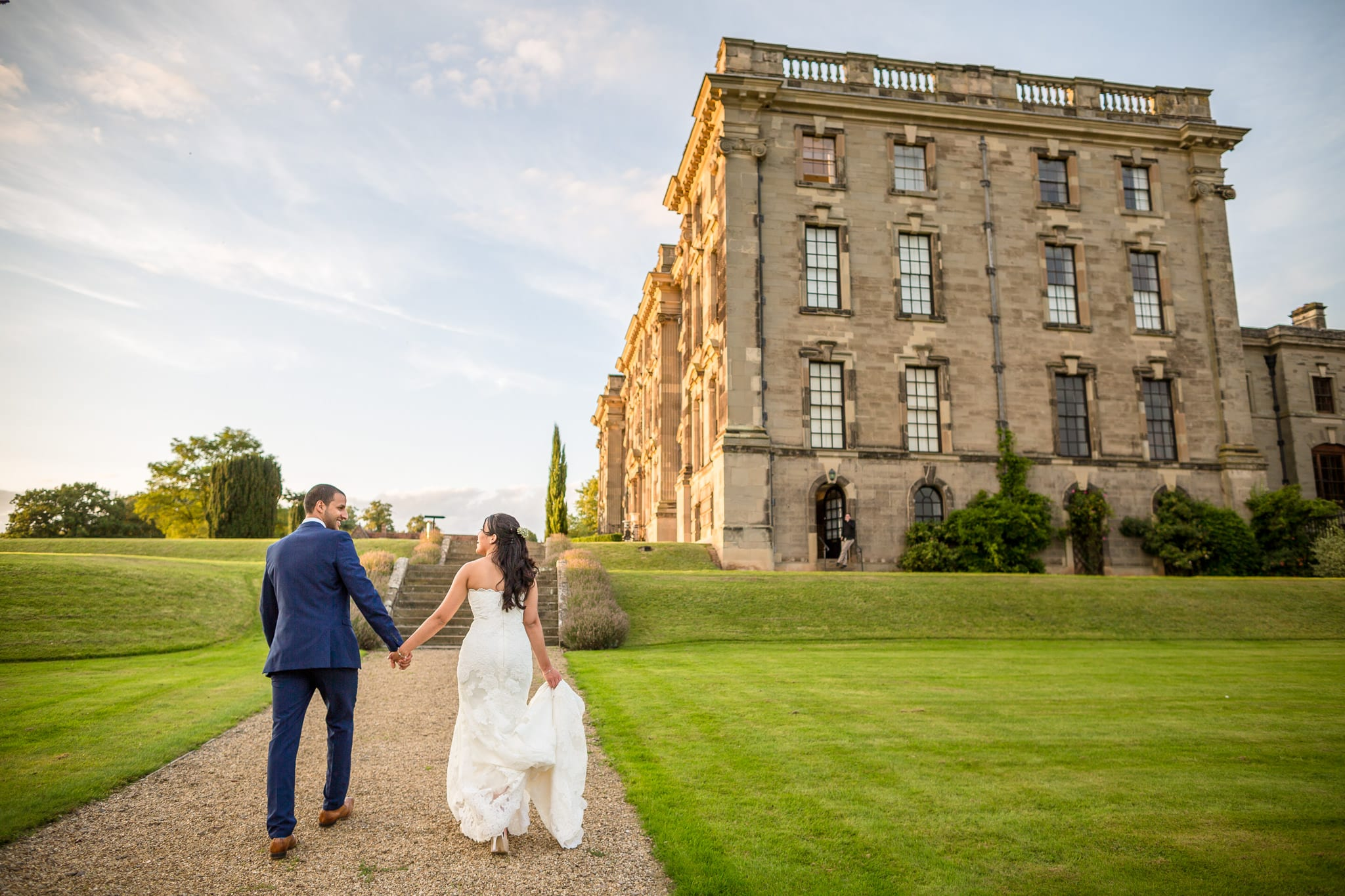 Bride and groom holding hands, walking towards a grand building. by Stoneleigh Abbey Wedding Photographer, S2 Images