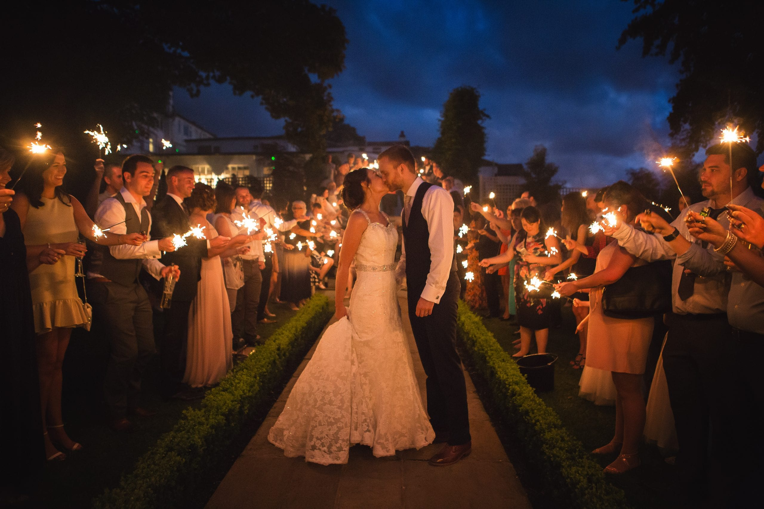 a bride and groom kissing whilst surrounded by guests with sparklers. By Warwick House wedding photographer S2 Images