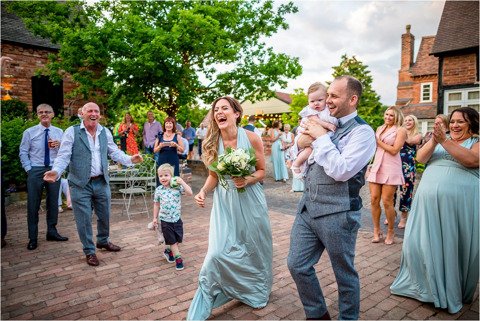 bridesmaid super happy to be given the brides bouquet instead of having to catch it - at curradine barns wedding venue in worcestershire