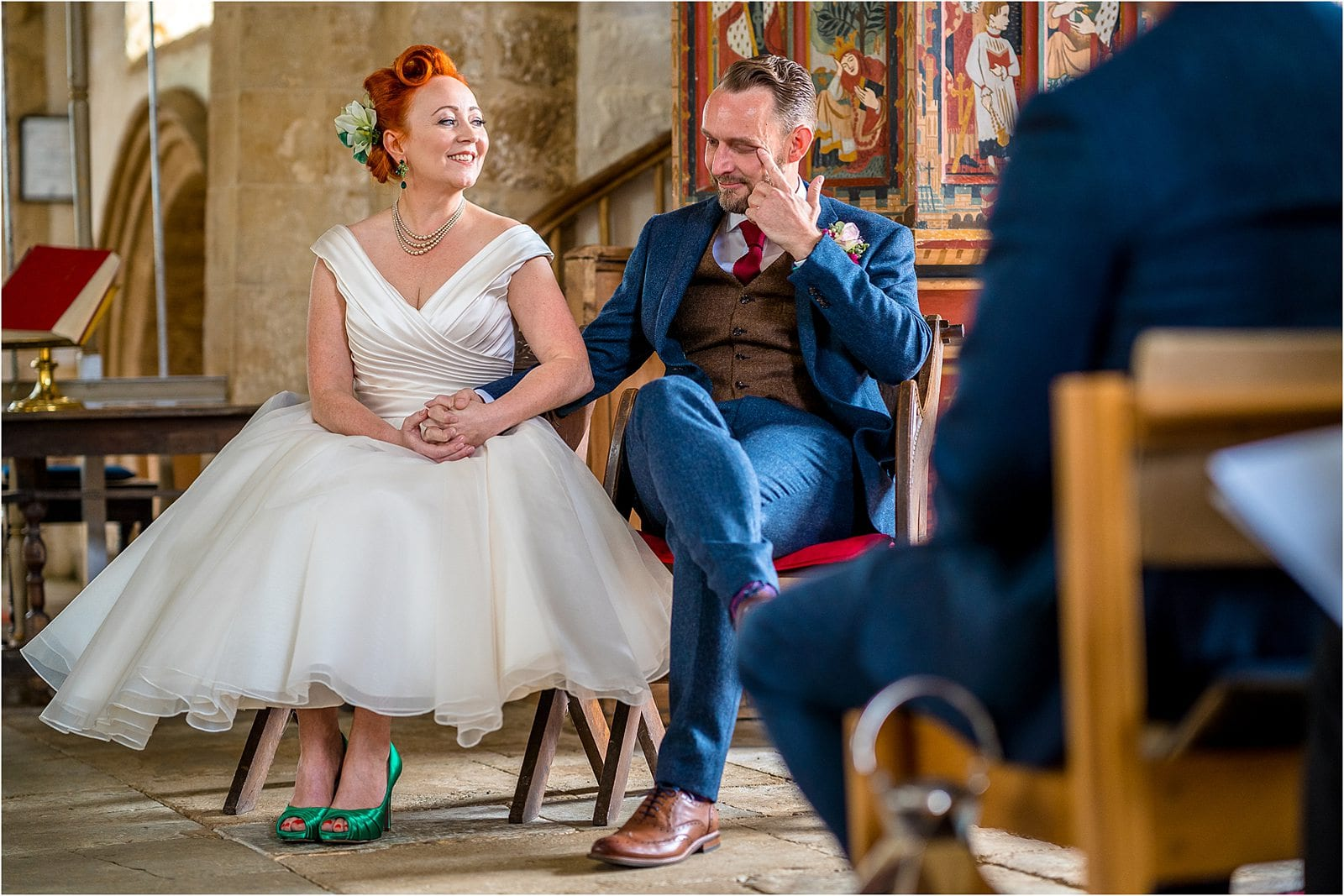 bride smiling at groom whilst he wipes a tear away - best wedding photography in warwickshire 2019