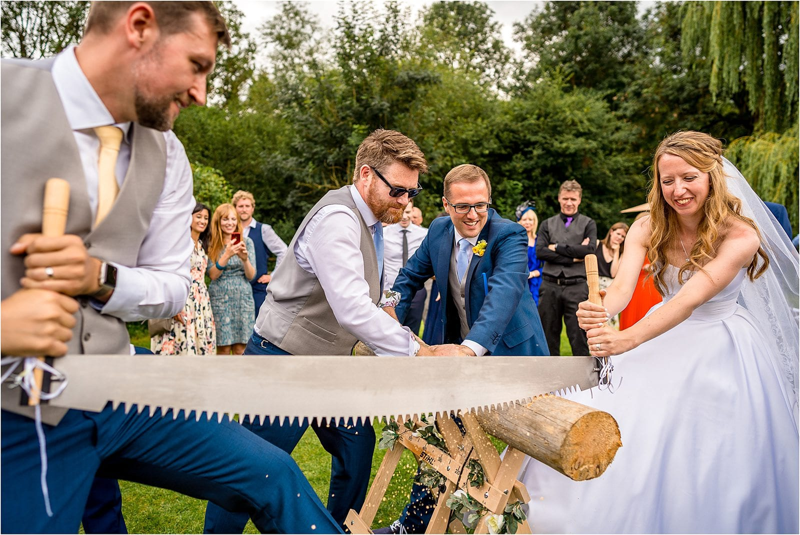 bride and groom sawing a log as a german tradition - best wedding photography in warwickshire 2019