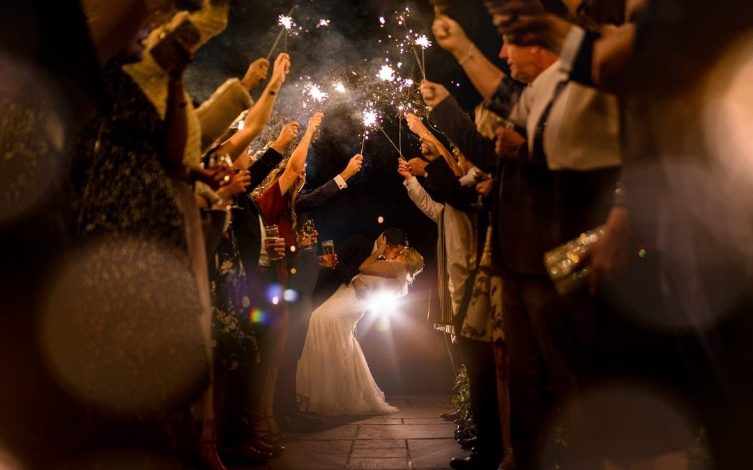 sparkler tunnel top tips - bride and groom kiss amongst loved ones holding sparklers
