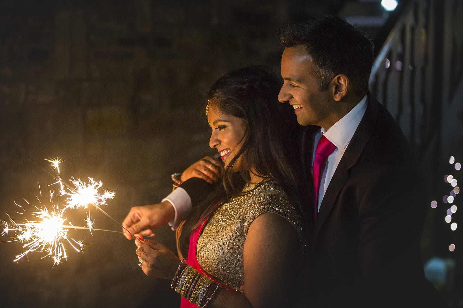 top tips for a perfect sparkler tunnel - bride and groom playing with sparklers